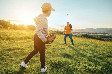 Photo for Father and son playing in baseball. Playful Man teaching Boy baseballs exercise outdoors in sunny day at public park. Family sports weekend. Father's day. - Royalty Free Image
