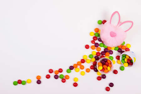 Photo pour Easter concept, candy pills, egg, pink bunny head toy on white background. Place for text - image libre de droit