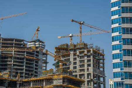 Photo pour Four high-rise buildings under construction. Big construction site with cranes and scaffolding in sunny day - image libre de droit