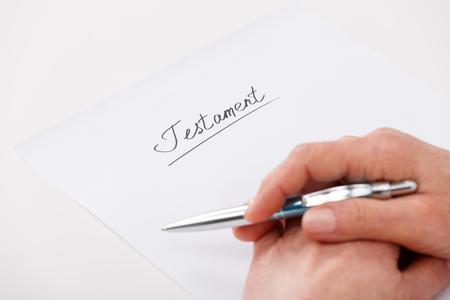 Hands of elderly woman writing ot paper testament