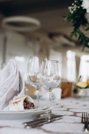 Photo pour Server table plate knife fork and wine glasses at the banquet. Luxurious elegant dinner at the table in the restaurant. Holiday table decoration - image libre de droit