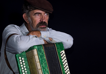 Portrait (low key) of an old country man with button accordion