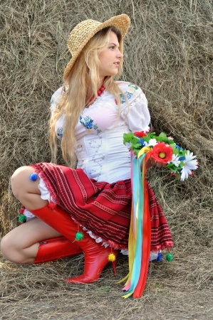 ukrainian teenage girl in traditional clothes near the haystack