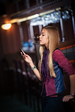 young woman sending sms on smartphone in the interior of the bar