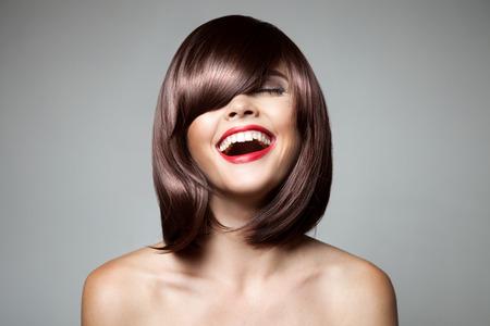 Foto de Smiling Beautiful Woman With Brown Short Hair. Haircut. Hairstyle. Fringe. Professional Makeup. - Imagen libre de derechos