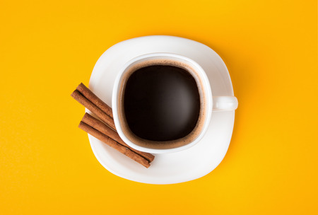 cup of fresh espresso on yellow background, view from above