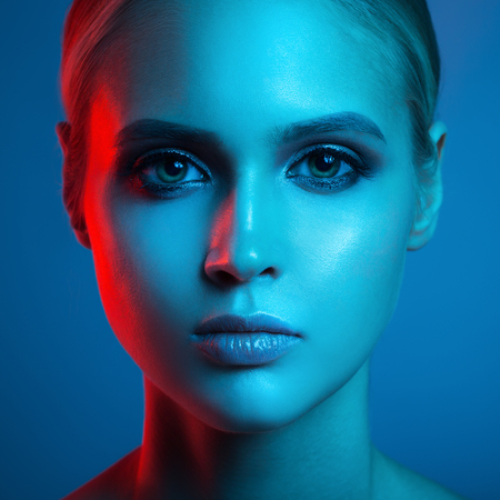 Foto de Fashion art portrait of beautiful woman face. Red and blue light color. - Imagen libre de derechos