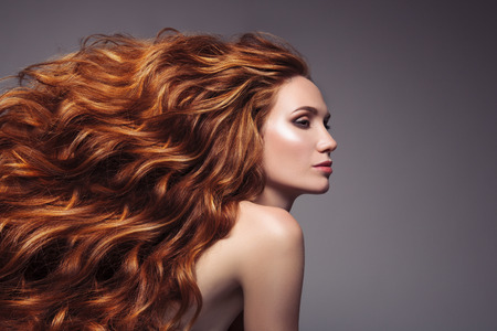 Foto per Portrait of woman with long curly beautiful ginger hair. - Immagine Royalty Free