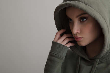 Photo pour Beautiful young girl dressed in a hoodie on a gray background - image libre de droit