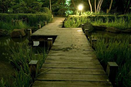 wooden bridge in japanese garden at night