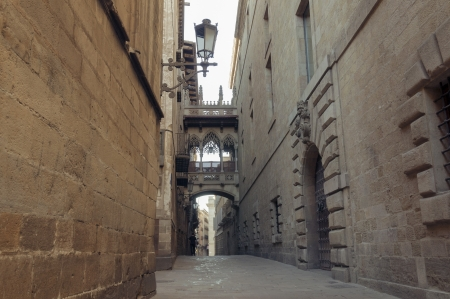 famous Gothic Quarter in barcelona with narrow medieval streets; focus on foreground wall