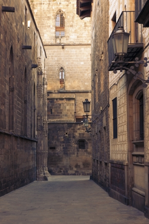 narrow space between tall medieval buildings in famous Gothic Quarter in Barcelona