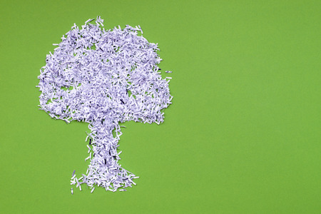 ecology recycle concept with big tree made from shredded white paper over green