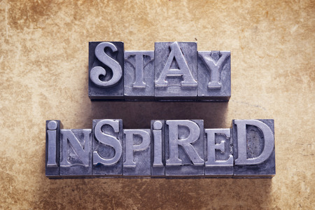 Photo for stay inspired message made from metallic letterpress type on vintage cardboard - Royalty Free Image