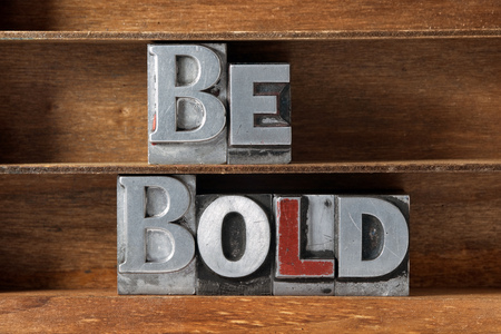 be bold phrase made from metallic letterpress type on wooden tray