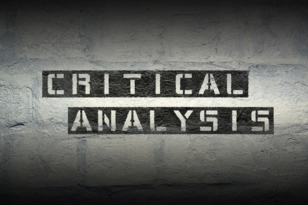 critical analysis stencil print on the grunge white brick wall