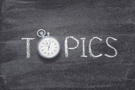 Foto de topics word handwritten on chalkboard with vintage precise stopwatch used instead of O - Imagen libre de derechos