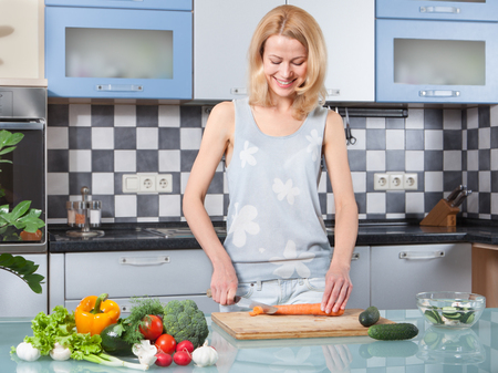 Photo for Young woman cutting vegetables in the kitchen - Royalty Free Image