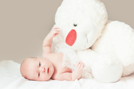 Photo for pretty newborn baby girl with a big soft toy lying on the blanket. - Royalty Free Image