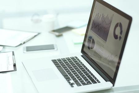 Photo pour laptop, clipboard and financial data on the businessman's Desk. - image libre de droit