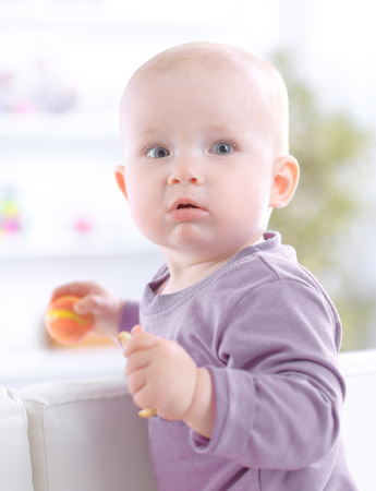 Photo pour close up.cute baby eating a cookie while sitting on the couch - image libre de droit