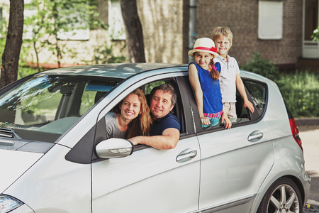 Photo pour Family with two children sitting in their family car. - image libre de droit