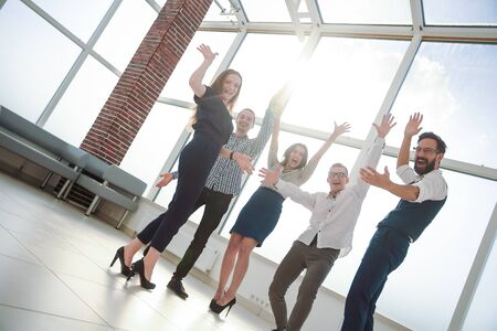 Photo pour Cheering business team standing in the office - image libre de droit