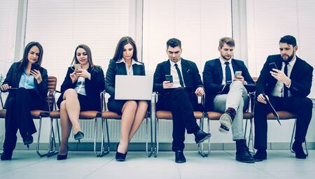 Foto per business team with laptop and smartphone sitting on the sofa in - Immagine Royalty Free
