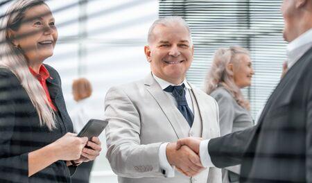 Photo pour close up. smiling business people greet each other with a handshake. - image libre de droit