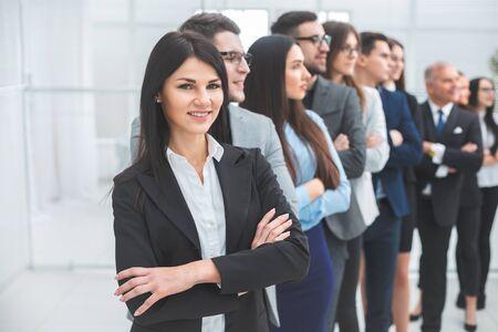 Foto de young business woman standing in front of her colleagues. the concept of teamwork - Imagen libre de derechos