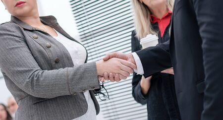 Photo pour businessman and businesswoman shaking hands at an office meeting - image libre de droit