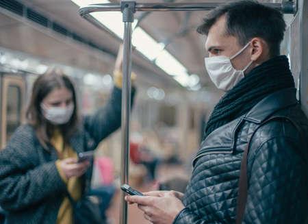 Photo pour passengers in protective masks standing in the subway car. - image libre de droit