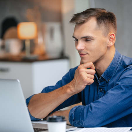 Photo for male freelancer works on a laptop in his kitchen. - Royalty Free Image