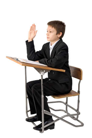 Schoolboy sit on the school-bench and raise one's hand