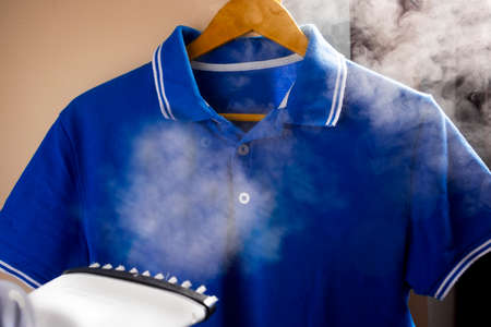 Photo pour Ironing and steaming clothes with an iron. Pants and tennis shirt. - image libre de droit