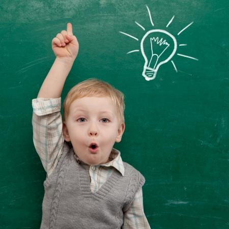 Foto de Cheerful smiling child at the blackboard  School concept - Imagen libre de derechos