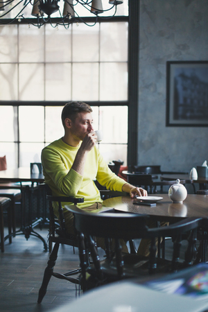 Adult man sits at a table in an empty cafe with a cup of coffee in hand