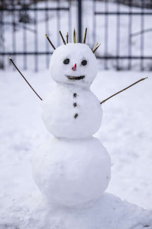 Photo pour Snowman in the backyard of the house with a red pepper nose. Vertical shot - image libre de droit