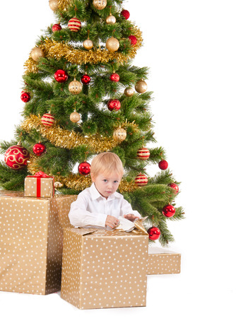 excitement little boy opening Christmas gift near New Year's tree