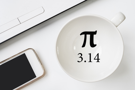 Happy Pi Day, written in black pen on white. On the desk a laptop, a cup, a hand holds the phone.