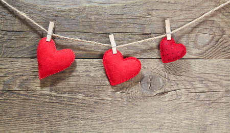 Photo for Felt red hearts hanging from a clothes line on wooden background - Royalty Free Image