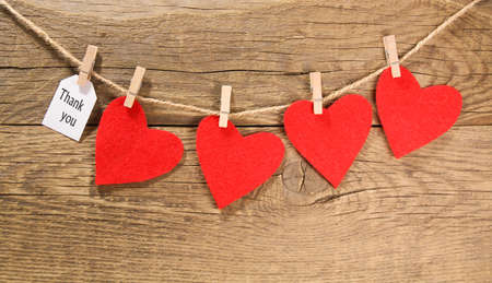 Photo for Appreciation with red hearts hanging from a clothes line on wooden background - Royalty Free Image