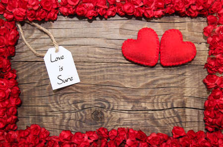 Photo for Love is sure hanging on line with flower frame - Royalty Free Image