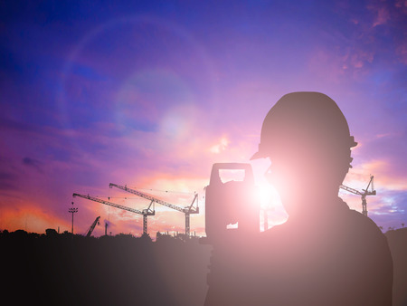 Silhouette Successful male engineer standing survey work on construction over blurred high-voltage pylons and construction. examination, inspection, survey