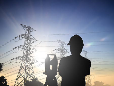 Silhouette Successful male engineer standing survey work on construction over blurred high-voltage pylons and construction. examination, inspection, survey, Industrial Land Scape