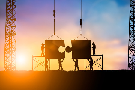 Photo pour Silhouette Team business engineer work connecting jigsaw puzzle pieces together over blurred natural background  pastel.Teamwork potential and motivate employee to growth:Business and people concept - image libre de droit