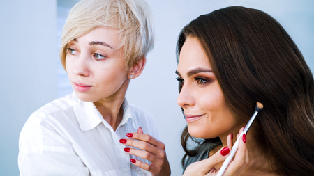 Foto per beauty salon artist doing professional makeup for young brunette woman - Immagine Royalty Free