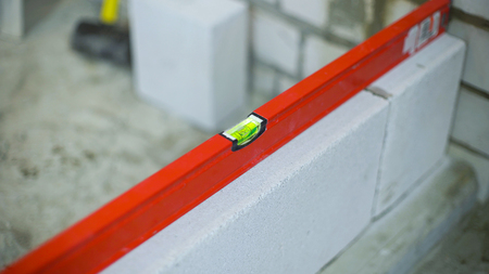 Photo pour checking evenness of aerated concrete wall with bubble level - image libre de droit