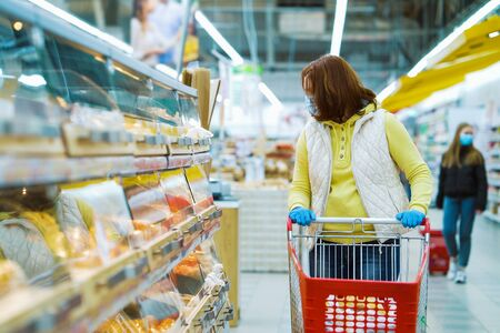 Photo pour Woman with shopping cart by shelves with fresh bakery during pandemic - image libre de droit