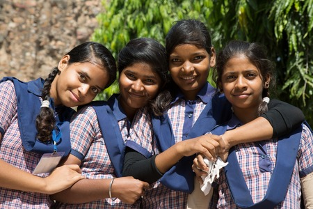 Photo for DELHI, INDIA - OCTOBER 11, 2015: unidentified local school girls for tour in Qutub Minar complex in Delhi, India. The girls  in school uniform have fun posing for a foto. Schools visit the famous landmarks as part of national education. - Royalty Free Image